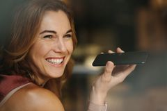 Woman talking over mobile phone. Closeup of a smiling woman talking over mobile phone looking away. Portrait of a smiling woman holding a phone in her hand Royalty Free Stock Images
