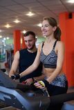 Smiling woman walking on treadmill with personal trainer Stock Photos