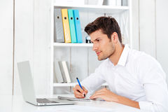 Closeup of smiling young businessman sitting and writing in notepad. At workplace Royalty Free Stock Photos