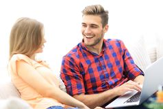 Closeup of a smiling young couple with laptop. On a light background Stock Image
