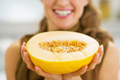Closeup on smiling young housewife holding melon slice Stock Images