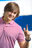 Closeup of smiling young man pointing up stock image