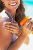 Closeup on smiling young woman applying sun screen creme Stock Photos