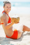 Closeup on smiling young woman on beach showing coconut Royalty Free Stock Image