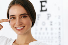 Closeup Of Smiling Young Woman In Front Of Visual Eye Test Board. Health And Visual Concept. Closeup Of Beautiful Smiling Woman With Healthy Eyes In Front Of stock photos