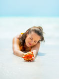 Closeup on smiling young woman laying on sea shore Royalty Free Stock Photography