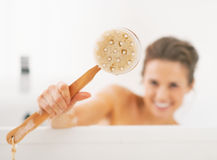 Closeup on smiling young woman showing body brush Stock Photography
