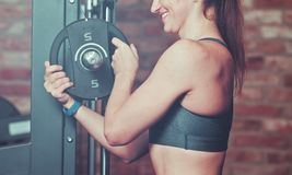 Closeup smilling athletic woman putting weight disk. To barbell  against brick wall in gym stock photos