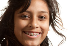 Closeup of a smily young girl with braces. Closeup of a young hispanic girl wearing colored braces.  Smiling at the camera. White background Stock Photography