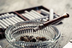 Closeup of smoke rising from a pipe in the ashtray Stock Photography