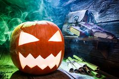 Closeup of smoking Halloween pumpkin on wooden desk Royalty Free Stock Images