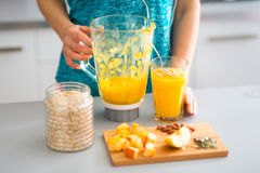 Closeup of smoothie with fresh fruits, seeds, nuts and oats. An elegant womans hand is resting against a blender, which is standing next to a full glass of a stock photography