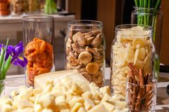 Closeup snacks, fresh flowers purple irises, dried fruits: figs, pear, apricot in glass vases, pieces parmesan cheese, cinnamon royalty free stock photography