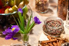 Closeup snacks, purple irises, fresh and dried fruits, red, white and black pepper mix in glass bowl, cinnamon sticks, nuts. stock images