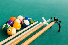 Closeup of snooker billards balls, chalk, cue and extender stick. On green table Stock Image