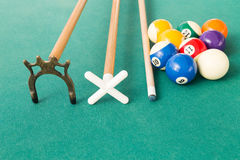 Closeup of snooker billards balls, cue and extender stick. On green table Stock Images
