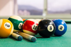 Closeup on snooker billards cue, chalk, balls on table. With green surface Royalty Free Stock Image