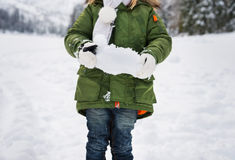 Closeup on snow in hands of child in green coat Stock Photos