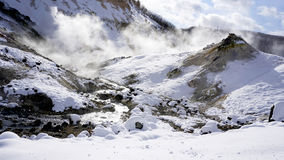 Closeup snow stone and stream in the mist Panorama Noboribetsu o Stock Photos