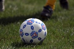 Closeup of soccer ball. Closeup of a soccer ball with soccer player shoes in the background during game Royalty Free Stock Photo