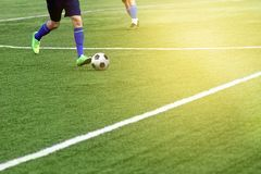 Closeup of a soccer ball and soccer player at the stadium. A beautiful football field with markings Royalty Free Stock Image