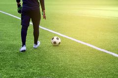 Closeup of a soccer ball and soccer player at the stadium. A beautiful football field with markings Stock Photo