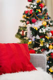 Closeup on sofa with pillow near Christmas tree. Closeup on sofa with red pillow in front of Christmas tree Royalty Free Stock Photography