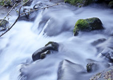 Closeup of soft waterfall. Waterfall with mossy rocks and soft water flowing down a mountain stream royalty free stock images