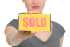 Closeup on sold sign holding by female isolated Stock Image