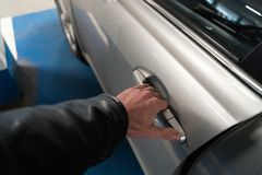Closeup som mäns hand på låser av en bildörr som öppnar den upp - bilen för ljus färg arkivbilder