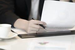 Closeup som räcker pennan för håll för affärskvinna och det finansiella dokumentet Arkivfoton