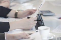 Closeup som räcker pennan för håll för affärskvinna och det finansiella dokumentet Royaltyfri Foto