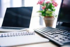 closeup som skjutas av den tomma läroboken, bärbara datorn, blommor i kruka, datoren, datortangentbordet och datormus royaltyfri foto