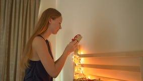Closeup som skjutas av en ung kvinna som förbereder en edvent kalender för jul lager videofilmer