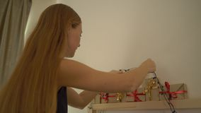 Closeup som skjutas av en ung kvinna som förbereder en edvent kalender för jul stock video
