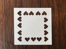 Closeup som skjutas av tomt papper för vit fyrkant som stansades i hjärtaform royaltyfri foto