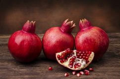 Still life. Juicy pomegranate with ruby red seeds. Closeup of some bright and juicy pomegranate with ruby red seeds on a rustic wooden table.Still life stock photos