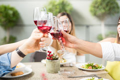 Closeup of some friends drinking wine. Group of friends making a toast with a glass of wine while eating in a restaurant, seen up close Stock Photo