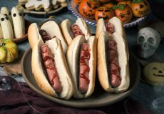 Funny halloween food on a rustic table. Closeup of some funny halloween food, such as hotdogs in the shape of bloody fingers, tangerines as carved pumpkins with royalty free stock photo