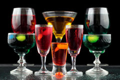 Closeup of some glasses with cocktails of different colors in nightclub.  Royalty Free Stock Photo