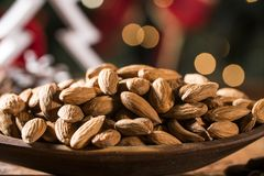 Closeup of some roasted almonds on rustic old wooden table with christmas background.  Royalty Free Stock Image