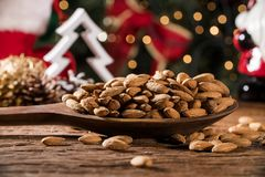 Closeup of some roasted almonds on rustic old wooden table with christmas background.  Stock Photos
