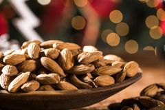 Closeup of some roasted almonds on rustic old wooden table with christmas background.  Royalty Free Stock Photos