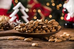 Closeup of some roasted almonds on rustic old wooden table with christmas background.  Royalty Free Stock Images