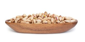 Pistachios. Closeup of some roasted Pistachios in a wooden bowl isolated on white background, Saving clipping paths royalty free stock image