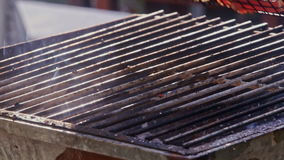 Closeup somebody roasts meat on open fire on barbecue grid. Closeup somebody roasts meat on open flame on metal barbecue grid and turns it over at daytime stock video footage