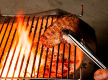 Closeup of someone turning a tasty steak cooking on a fire Royalty Free Stock Photography