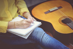 Closeup songwriter writing on note paper with acoustic guitar ne. Closeup songwriter having fun enjoy hobby concept and writing on note paper with acoustic royalty free stock images