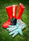 Closeup of spade, gloves and red rubber boots lying on grass Royalty Free Stock Images