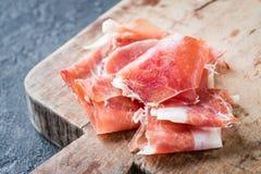Closeup of Spanish ham jamon serrano or Italian prosciutto crudo. On old wooden board Stock Photos
